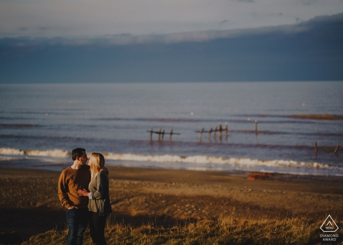 Beach Engagement Photography - A couple embrace at last light on the cliffs at Happisburgh in Norfolk, UK