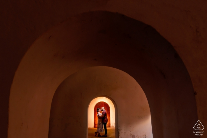 El Morro, San Juan PR Engagement Portrait of a Couple - Image contains:Framing the couple with the arches and the door behind couple.