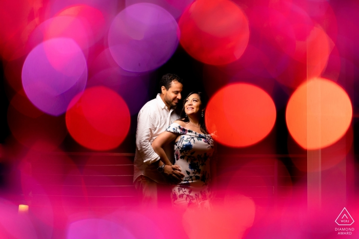 Courtyard by Marriott, Isla Verde PR Engagement Picture Session - Portrait contains: Champagne Glasses to create bokeh that frames the couple