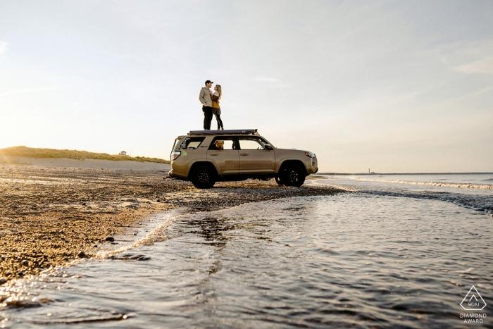 Cape Cod, MA Engagement Photo d'un couple - le portrait contient: 4x4, plage, sable, vagues, eau