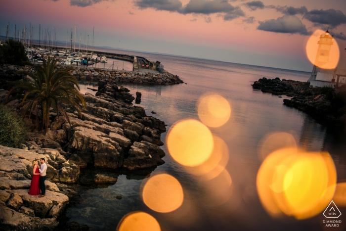 Session du phare de Cascais - Portrait de fiançailles d'un couple - L'image contient: bokeh, rochers, eau, plage, crique, robe rouge