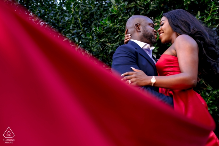Chicago Engagement Portrait of a Couple - Image contains:red dress, green, trees, blue suit, embrace
