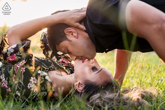 Allemagne Couple faisant le baiser de Spider-Man | Photo de fiançailles d'un couple - Le portrait contient: herbe, couchée, à l'envers, chemise noire, cheveux