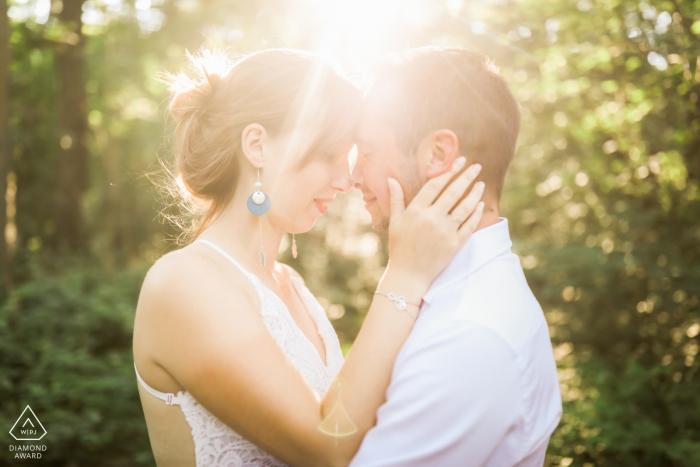 Rambouillet, Yvelines - France Photo rétro-éclairée d'un couple amoureux se touchant la tête dans une forêt - Séance de portraits de fiançailles - L'image contient: soleil, lumière, lumière du soleil, soleil, arbres, étreinte