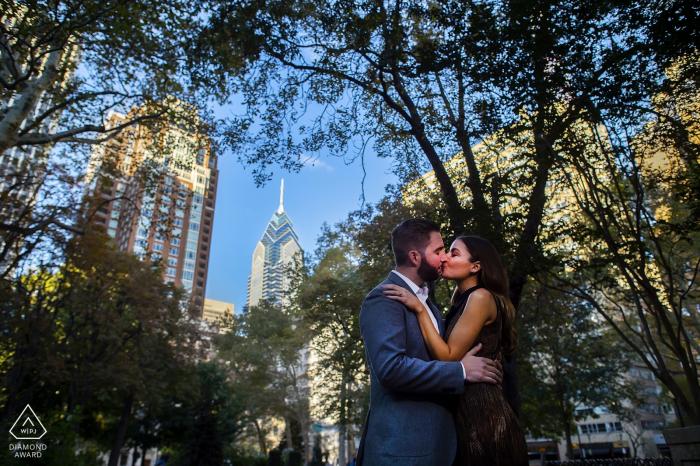 Un couple fiancé partage un baiser au Rittenhouse Square à Philadelphie. PA Engagement Photography - Portrait contient: bâtiments, arbres, parc, arbres, ciel