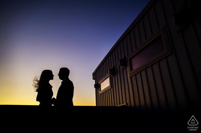 Les futurs mariés partagent un câlin à Philadelphie. - Silhouette PA, sombre, coucher de soleil, vent, cheveux, souffle