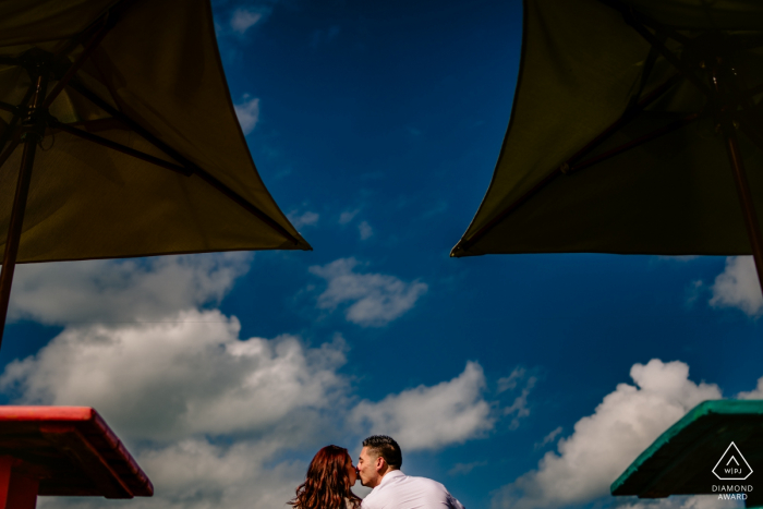 Sunset Pier,Key West, FloridaEngagement Photographer: Used the bar tops and umbrellas to create symmetry, while I used the blue sky for a clean background