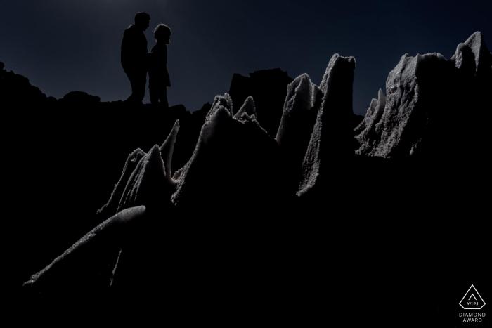 Atacama desert couple silhouette framed in ice floe during engagement photo session.