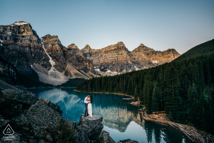 Moraine Lake, Banff National Park, AB, Canada | Golden hour before the sunrise | Engagement Couple Photography - Portrait contains:water, mountains, cliff, view, hug