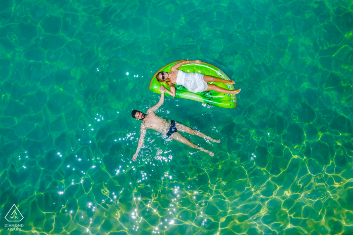 Carlentinisummer loving - engagement portrait shot with overhead drone of a couple relaxing in the water.
