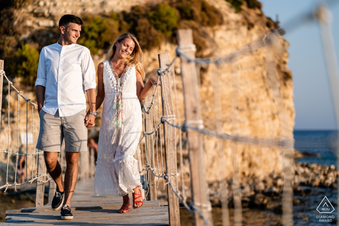 Walking on the wood bridge - A couple posing for engagement portraits in Zakynthos, Greece