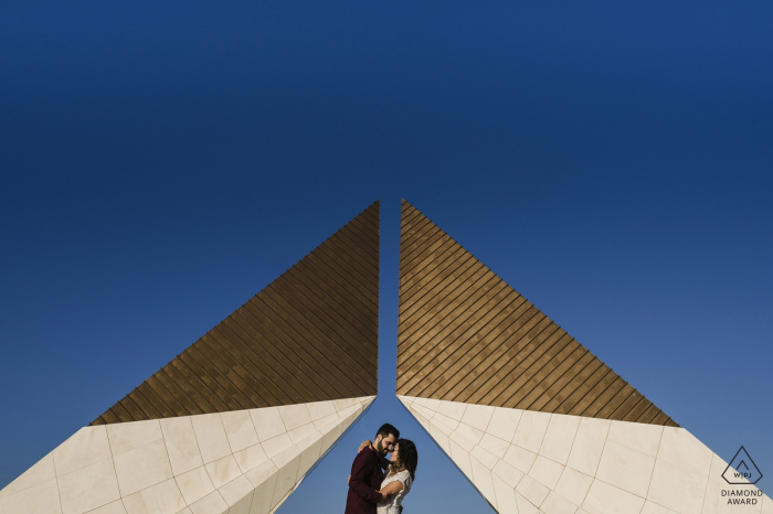 Lisbon Engagement Photographer: An early sunrise at Lisbon, challenge the couple to be on the monument and give a kiss, but when they are going there, right on the middle they starting acting super natural, and i make the shot