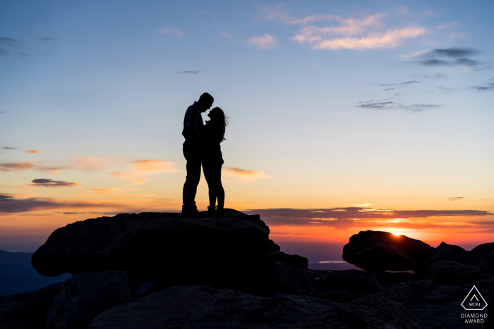 Mt Evans CO Couple on mountain top at sunrise - Hiking to make great engagement photos