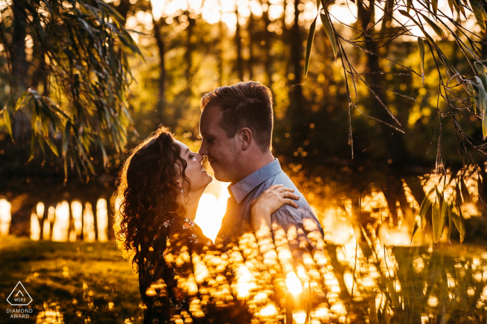 Couple is snuggling around sunset time during engagement session at sint-niklaas private territory