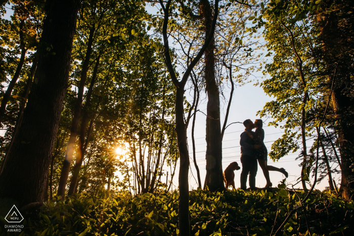 sint-niklaas private territory engagement photographer: couple is kissing silhouetted by the sun and sky