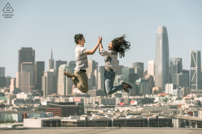 San Francisco, CA engagement shoot with a Couple jumping in the air, city in the background.