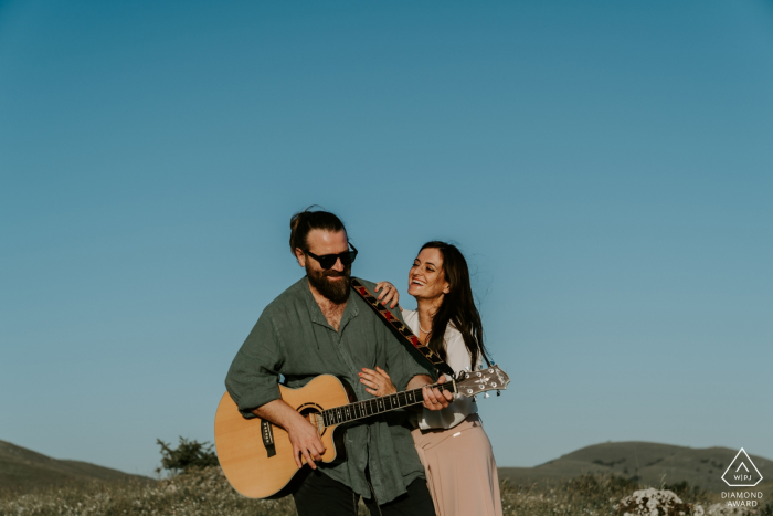 Mountains in Abruzzo - Italy | He plays the guitar for her during an engagement shoot under the blue sky