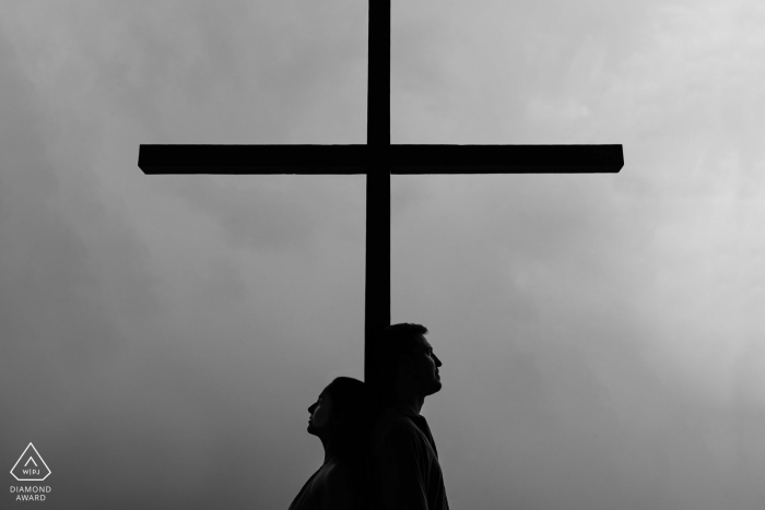 Belo Horizonte, Brazil Silhouette of the couple together with the cross during engagement portrait shoot.