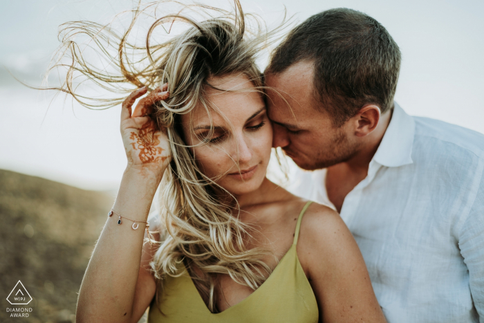 A couple with their hair blown in the wind during engagement portraits in Désert d'Agafay