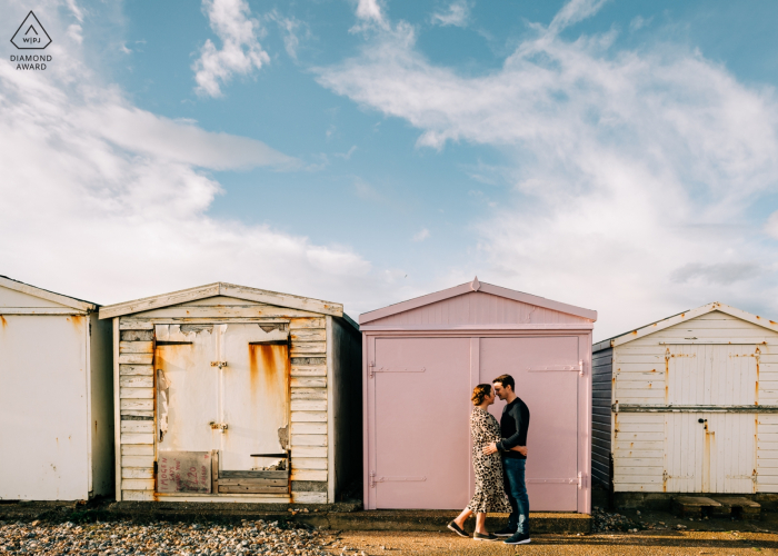 Shoreham Beach, West Sussex, UK engagement photography of a Couple embracing by the beach huts on Shoreham Beach