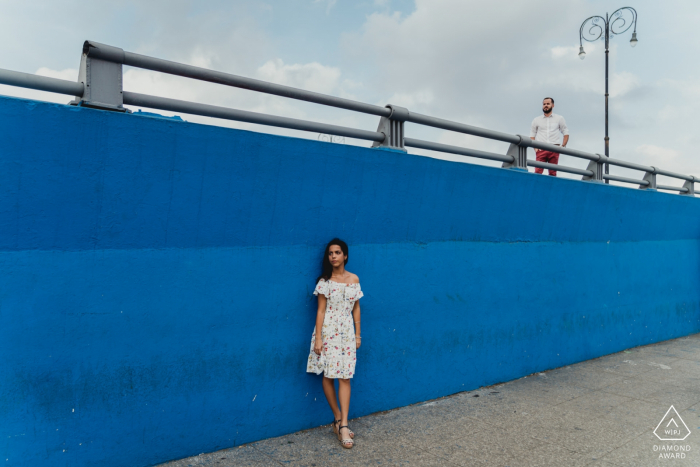 Cuba engagment shoot against a highway wall that is painted blue.