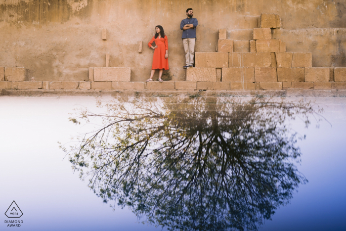 Ahmedabad, India engagement photographer: Couple stood on a ledge with a tree reflected underneath them (signifying roots to their marriage/relationship)