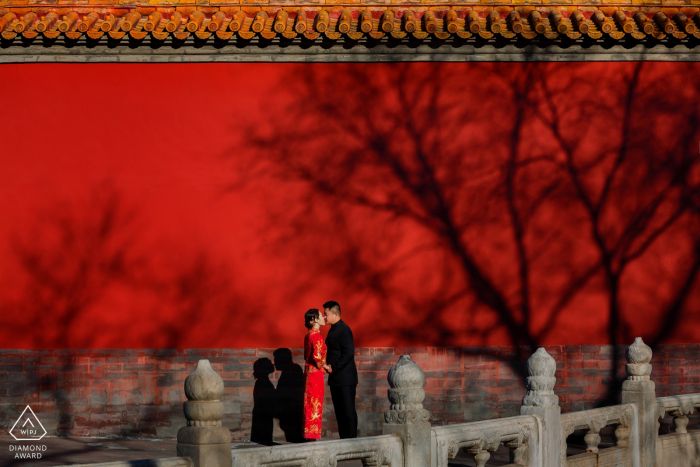 Beijing Fiery love engagement pre-wedding photo shoot in red dress against red wall.