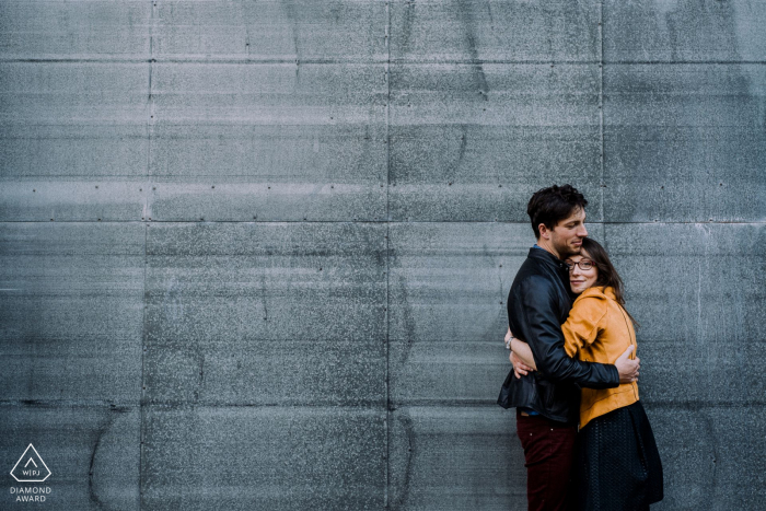 A couple giving a hug in front of a metallic wall in Honfleur, France