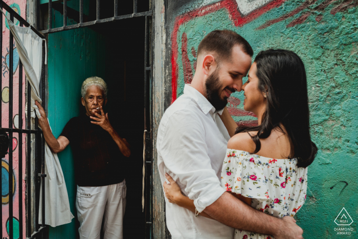 Cuba engagement shoot of a couple holding each other while an onlooker watches.