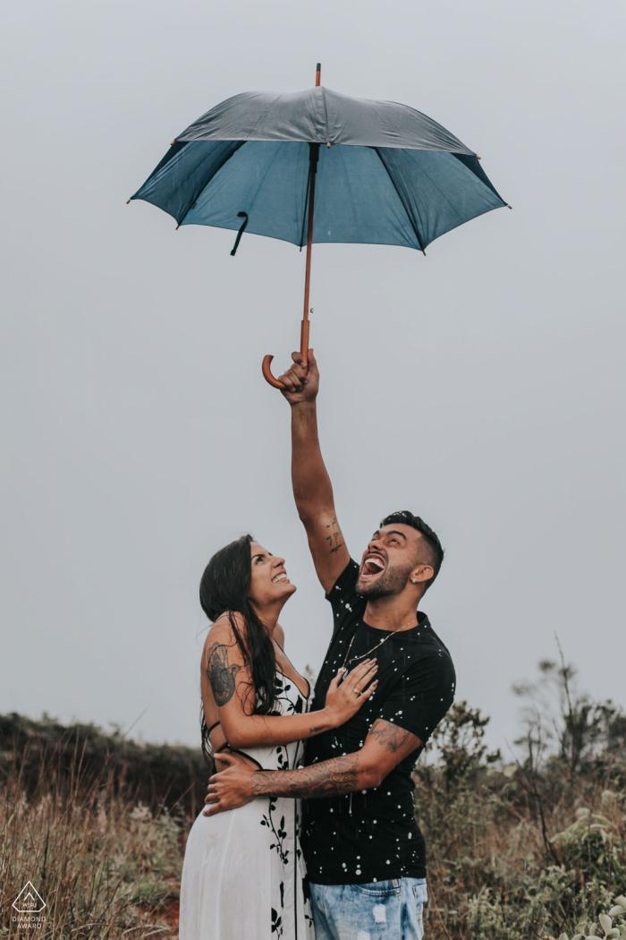 Belo Horizonte, Brazil couple holding an umbrella and enjoying their engagment photo session.