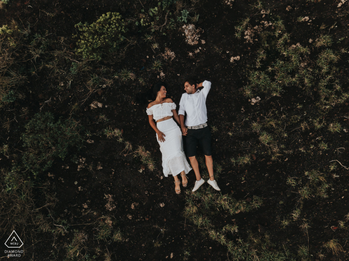 Belo Horizonte, Brazil - Engagement picture taken from an overhead drone of a couple lying down on their backs.