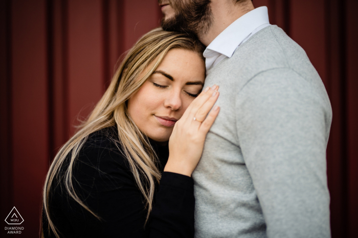 Rotterdam engagement picture against a red background - Couple embracing