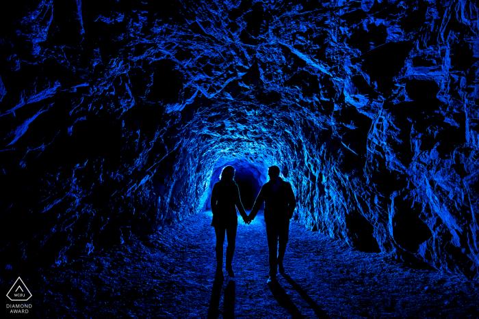 Bride and groom-to-be walking through dark tunnel in Canon City, Colorado.
