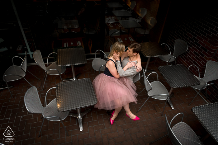 Engagement image of a couple sitting in silver chairs in cafe Yorkville, Ontario.