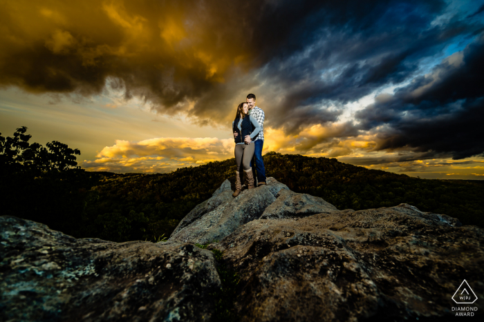 """Photographer:""""This rock formation is the staple of this park and the sky always has some incredible color around sunset. My assistant held a flash to help brighten the couple so I could darken down the rest of the scene and pull out the drama in the sky."""""""