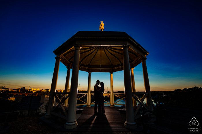 "Photographer: ""This gazebo is on the backside of the Art Museum and we lucked out with some great colors in the sky that morning. I used a flash behind the couple to give them a slight rim light so they would pop against the background."