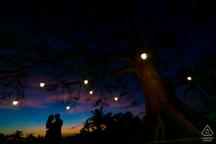 Dorado, PR pre wedding photographer: Using sunset to pop the silhouette of couple while framing with the tree lights.