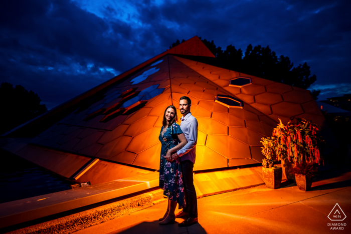 Couple Engagement Photo Session | Denver Botanic Gardens, Denver, CO - An engaged couple poses in front of a pyramid with dramatic lighting