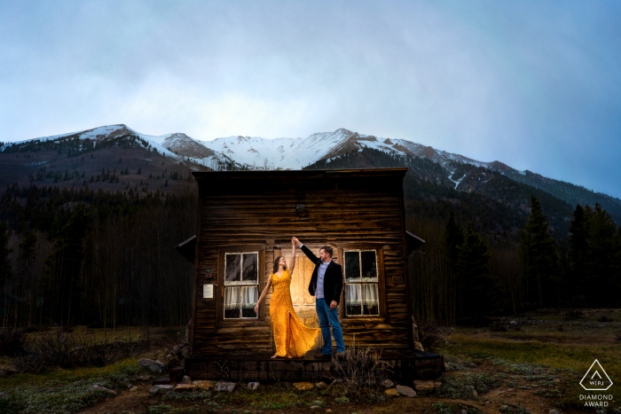 The gentleman twirls his fiance in front of an abandoned schoolhouse, which is part of a Ghost Town in rural Winfield, Colorado.