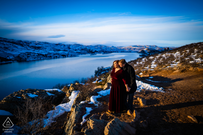 A couple share an intimate moment while trying to stay warm as the sunsets during their winter engagement session at Horsetooth Reservoir in the foothills of Fort Collins, Colorado.