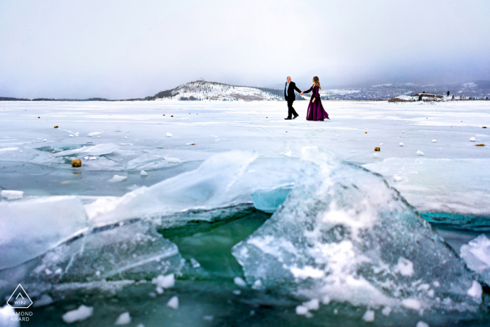 A couple walks hand-in-hand as they take a stroll along frozen Lake Dillon on a windy winter day near Silverthorne, Colorado during their engagement session.