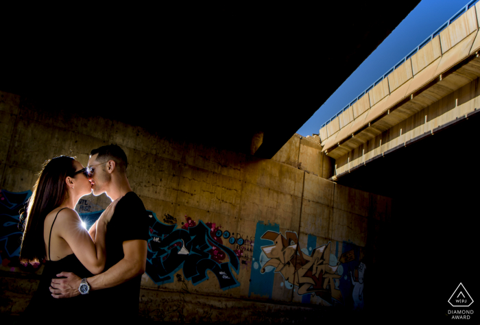 A couple kiss in the shadows of a bridge in Aguilas, Spain