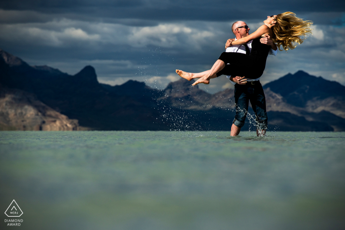 Bonneville Salt Flats engagement shoot of a couple goofing around in the water