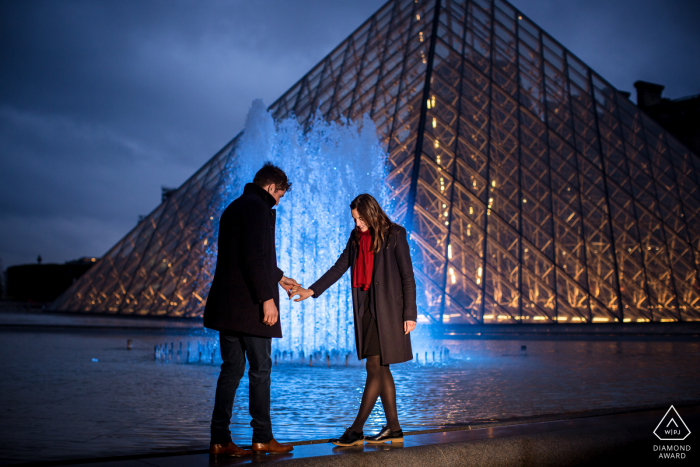 Louvre pyramid engagement photo shoot of a couple with a water fountain glowing behind them.