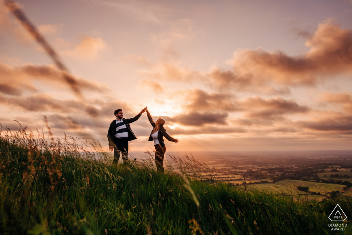 Couple dancing on hilltop at sunset at the Devil's Dyke, near Brighton, UK