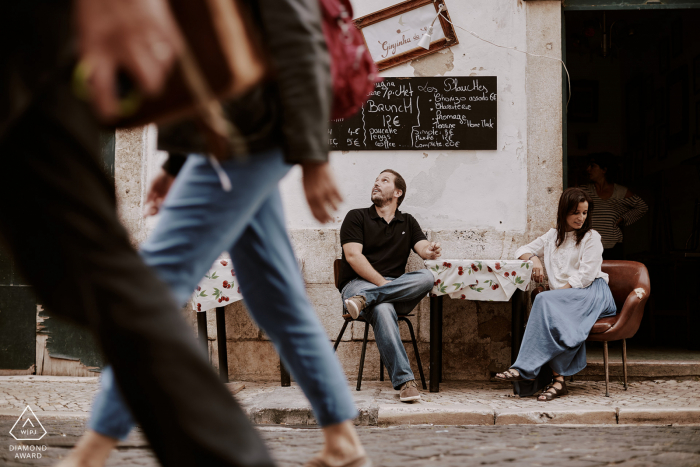 The engaged couple sits at a terrace in front of a traditional tavern in the streets of Alfama, Lisboa.