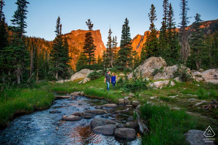 The couple stroll in Rocky Mountain National Park at sunrise, with hallet peak lit up gold with dawn's light   Dream Lake, Rocky Mountain National Park, Colorado Portraits