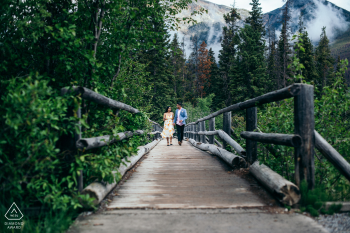 an engaged couple are Running together across a bridge in Pyramid Island, Jasper National Park, AB, Canada