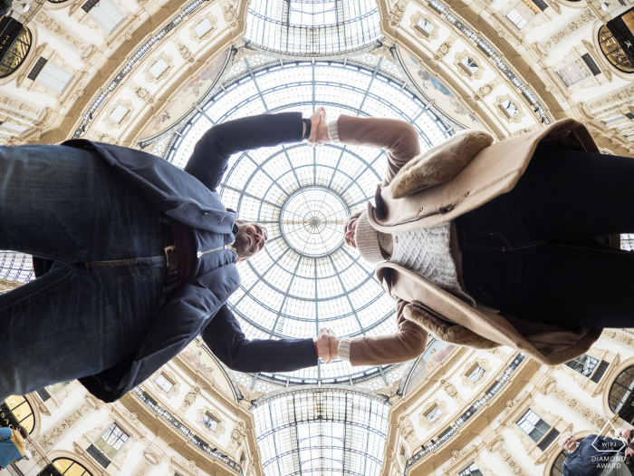 Milano, Italy low angle engagement portrait looking up at the kissing couple