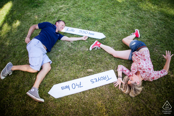 A couple with their native town signs lying on the grass lawn of Nougaroulet, Gers, France